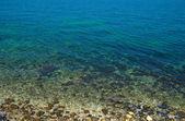 Pobřeží s kameny a modrý oceán vody. — Stock fotografie