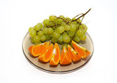 Green grapes and orange isolated on white. — Stock Photo