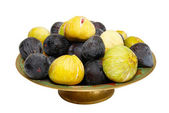Stack of black and yellow figs on the plate isolated on white. — Stock Photo