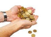Många mynt i kupade händer isolerad på vit. — Stockfoto