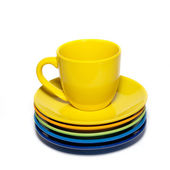 Yellow teacup and stack of saucers isolated on white. — Stock Photo