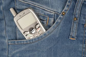 Cell phone in pocket of blue jeans. — Stock Photo