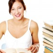 Smiling girl sitting near the pile of books. — Stock Photo #7647869