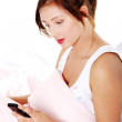 Teen girl in bed reading sms. — Stock Photo