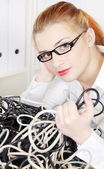 Young woman holding tangle of cables. — Stock Photo