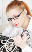 Young woman looking at tangle of cables. — Stock Photo