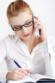 Businesswoman answering the phone and writing. — Stock Photo