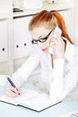 Beautiful businesswoman answering the phone and writing. — Stock Photo
