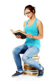 Teen student reading a book sitting on books. — Stock Photo