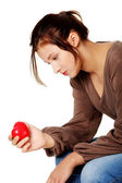Sitting girl with broken heart looking at the heart. — Stock Photo