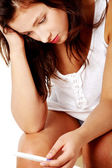 Closeup portrait of young depressed girl checking pregnant test. — Stock Photo