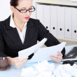 Businesswoman reading files near crumpled files. — Stock Photo