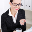 Businesswoman holding pills and water. — Stock Photo