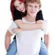 Handsome man giving a piggyback ride to his girlfriend. — Stock Photo