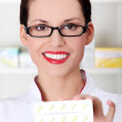 Pharmacist showing pill blister. - Stock Photo