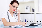 Female doctor talking by the phone and writing. — Stok fotoğraf