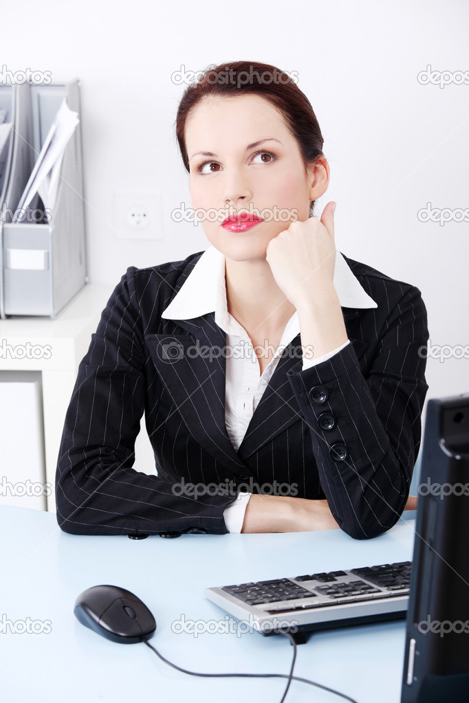 Portrait of a beautiful business woman sitting behind the desk trying to work out a solution for the problem. — Stock Photo #7841884