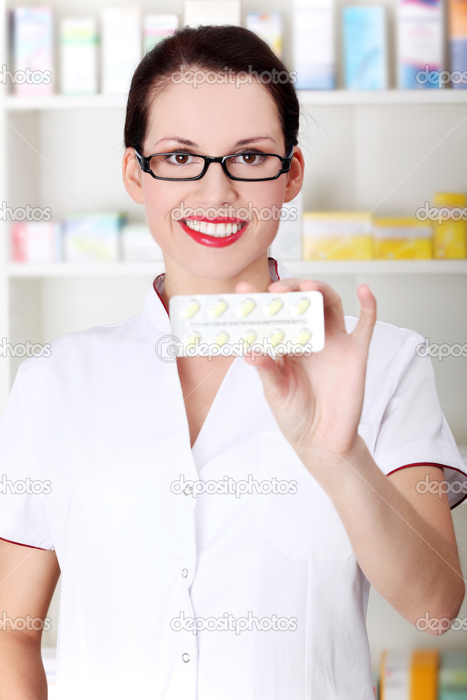 Pretty caucasian pharmacist showing pill blister. — Stock Photo #7847814