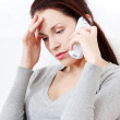 Worried woman sitting on a sofa, talking on a phone. — Stock Photo #7857036
