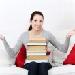 Smiling female student holding a pile of books. — Stock Photo