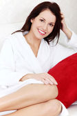 Beautiful woman sitting on a sofa in a dressing-gown. — Stock Photo