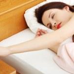 Beautiful woman turning off an alarm clock in the morning. — Stock Photo