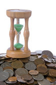 Coins and hourglass — Stock Photo