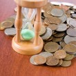 Stock Photo: Coins and hourglass