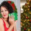 Black Woman Opening a Christmas or birthday present - Stock Photo