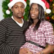 Black Couple wearing Christmas Santa Hats - Stock Photo