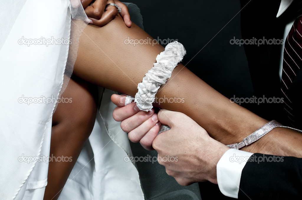 Caucasian man removing the garter from a newly married black African American woman — Stock Photo #7904832