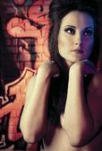 Naakt vrouw in de buurt van de graffiti muur — Stockfoto