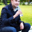 Young man relaxies in the park at lunch time - Stock Photo
