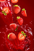 Strawberry falling into the lot of juice — Stock Photo