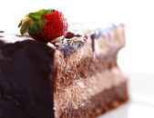 Slice of tasty chocolate cake with strawberry on top — Stock Photo