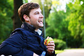 Young man relaxies in the park at lunch time — Stock Photo
