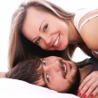 Smiling couple relax in bed - Stock Photo