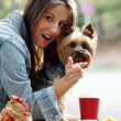 Woman have lunch while strolling with her dog — Stock Photo