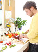 Young and cheerful man cooking — Stock Photo