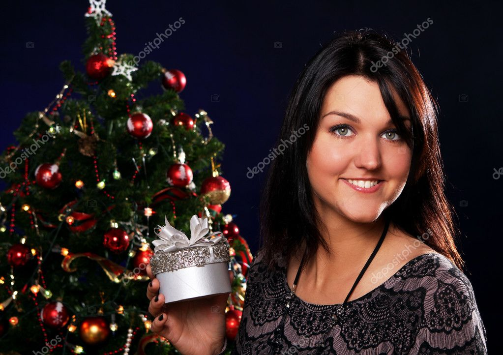 Happy and smiling woman with Christmas gift in hands — Stock Photo #7182070