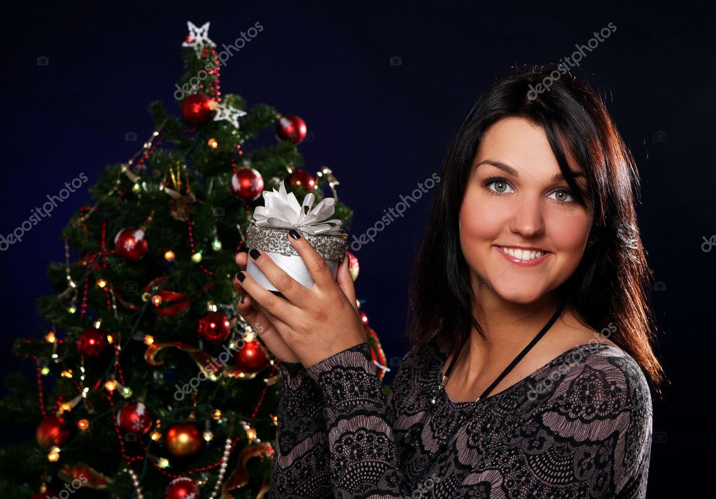 Happy and smiling woman with Christmas gift in hands — Stock Photo #7182073
