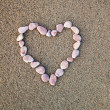 Heart of pebbles inlaid on a background of sand — Stock Photo