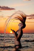 Una chica joven en el mar con una hermosa salpicaduras de agua — Foto de Stock