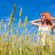 Beautiful young woman at wheat field — Stock Photo