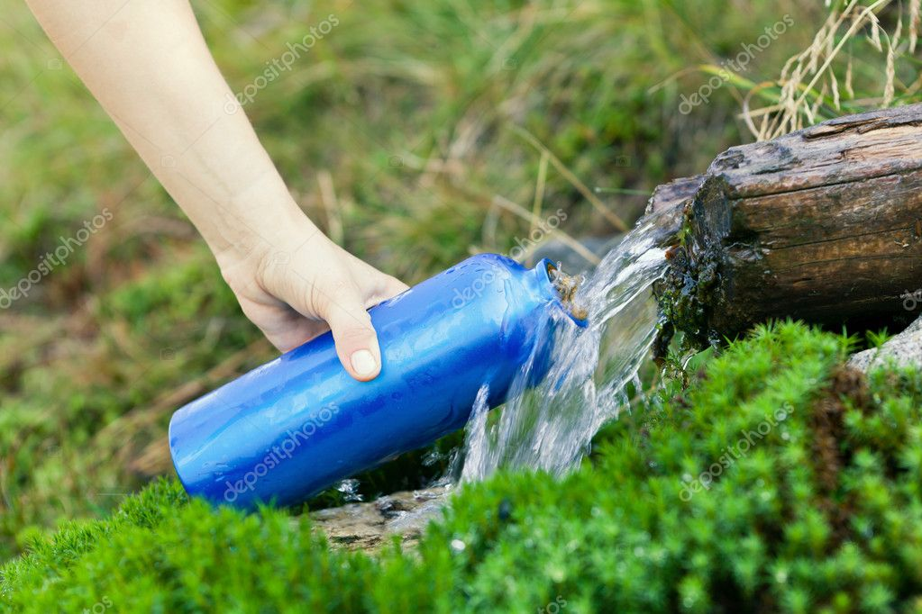 Woman filling water bottle from stream on hiking trip — Stock Photo #6840826