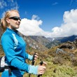 Woman nordic walking in mountains - Stock Photo