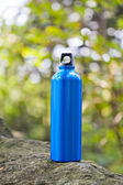 Water bottle in green forest — Stock fotografie