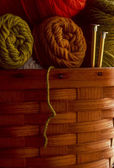 Wool yarn in a basket with knitting needles — Stock Photo