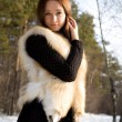 Young girl in a fur vest in snowy woods - Stockfoto