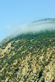 Small cloud born on the top of cliff — Stock Photo